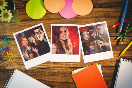 hedonistic: Overhead view of office supplies with blank instant photos against happy friends having fun together Stock Photo