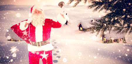 adult footprint: Santa claus holding a sack and bell against cute village in the snow Stock Photo