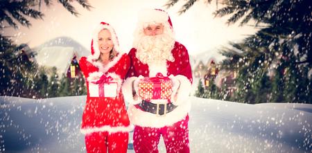 se�ora: Santa y se�ora Claus sonriendo a la c�mara regalo de ofrecimiento contra lindo pueblo en la nieve Foto de archivo
