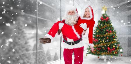 señora: Santa y señora Claus sonriendo a la cámara contra la casa con el árbol de navidad