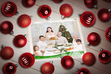Christmas baubles on table against a happy family christmas card photo