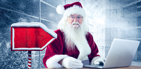 pays: Santa pays with credit card on a laptop against window overlooking snowy forest