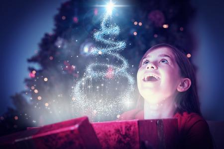 Meisje dat een magische kerstcadeau opent tegen kerstboomontwerp