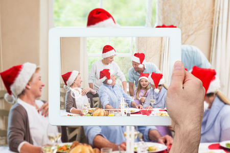 extended family: Hand holding tablet pc against  happy extended family in santa hat speaking together Happy extended family in santa hat speaking together at home in the living room
