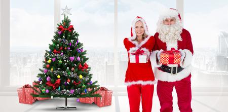mrs: Santa y se�ora Claus sonriendo a la c�mara ofrecer regalo contra casa con el �rbol de navidad
