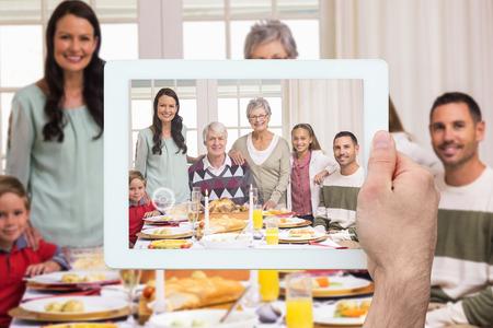 Une main tenant la tablette pc, contre la famille élargie heureux au dîner de Noël posant la caméra Banque d'images