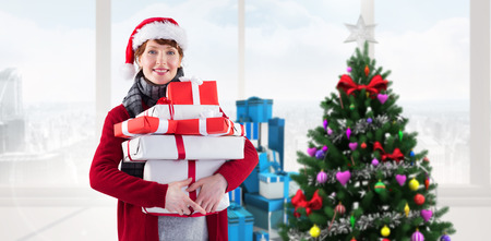christmas tree presents: Smiling woman holding christmas presents against home with christmas tree Stock Photo
