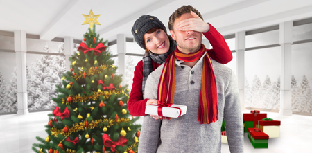 Woman giving man a present against home with christmas tree