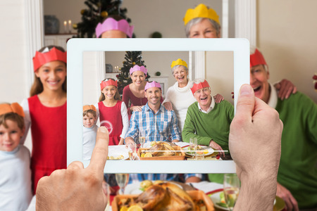 Hand holding tablet pc against happy extended family in party hat at dinner table Stock Photo