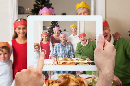 abuelo: Mano que sostiene la PC de la tableta contra la feliz familia extendida en sombrero de fiesta a mesa