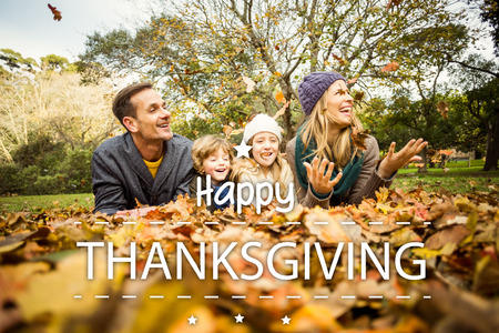 Happy thanksgiving against smiling young family throwing leaves around Stock Photo