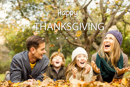 lying on leaves: Happy thanksgiving against smiling young family throwing leaves around Stock Photo
