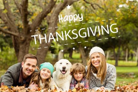 Glückliche Danksagung gegen junge Familie mit einem Hund
