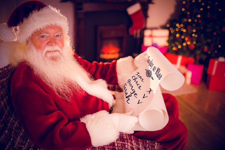 naughty or nice: naughty or nice against smiling santa claus reading his list Stock Photo