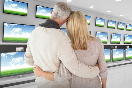 arms around: Rear view of couple with arms around against televisions for sale