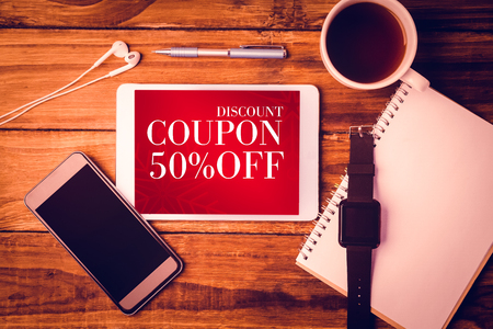 coupon: Sale advertisement against tablet and smartphone and swatch on notepad next to cup of coffee