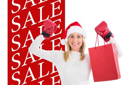christmas savings: Festive blonde in boxing gloves with shopping bag against sale advertisement