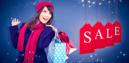 Happy brunette in winter clothes holding shopping bags against blue background Stock Photo