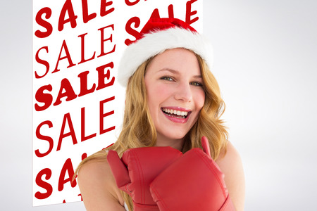 christmas savings: Smiling blonde wearing red boxing gloves against sale advertisement Stock Photo