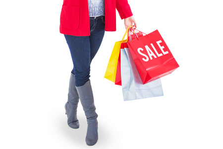 Happy blonde in winter clothes holding shopping bags against sale