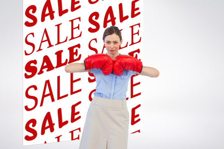 tough: Tough businesswoman posing with red boxing gloves against sale advertisement