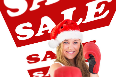 christmas savings: Festive blonde punching with boxing gloves against sale advertisement Stock Photo
