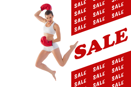 brown haired: Motivated fit brown haired model in sportswear jumping against sale advertisement