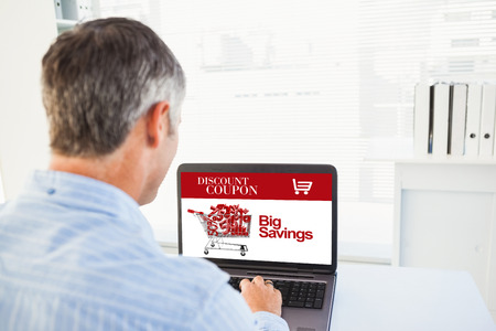 grey hair: Man with grey hair using his laptop against sale advertisement Stock Photo
