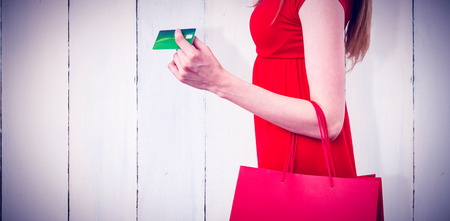 Woman shopping with her credit card against wooden planks Stock Photo