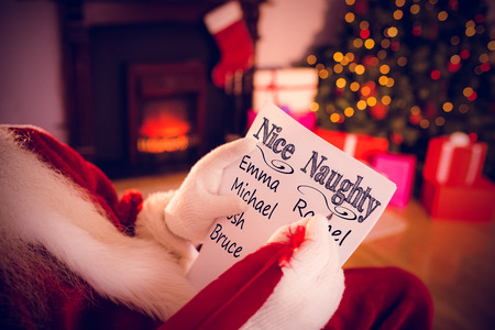 naughty or nice: naughty or nice against santa claus writing list with a quill