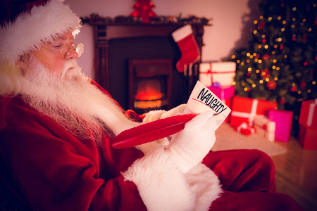 naughty or nice: naughty or nice against santa claus writing list on scroll Stock Photo