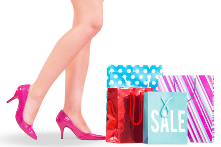 gift spending: Womans legs in high heels with shopping bags against sale