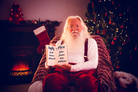 naughty or nice: naughty or nice against santa claus showing his book Stock Photo