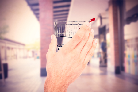 hand out: Businessman holding hand out in presentation against shopping cart