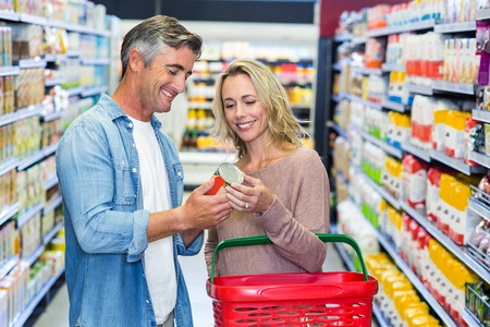 shopping store: Smiling couple holding canned food at supermarket