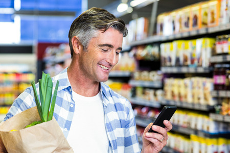 sac �picerie: Smiling man with grocery bag using smartphone at the supermarket Banque d'images