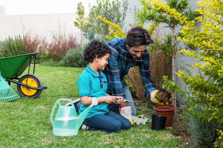 gardening tools: Smiling father and son gardening together