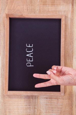 garabatos: Vista de la mano haciendo signo de la paz en el escritorio
