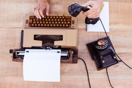 old desk: Above view of typewriter and old phone on wooden desk Stock Photo