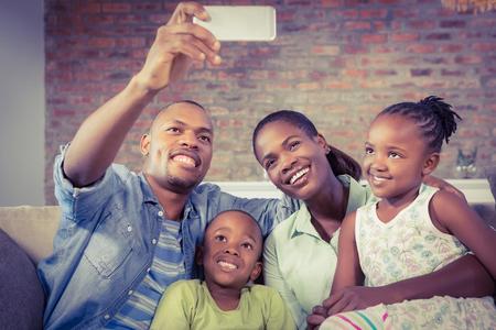 Famille heureuse de prendre une selfie sur le canapé dans le salon Banque d'images