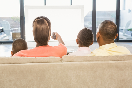 pareja viendo television: Más de hombro vista de la familia informal viendo la televisión en la sala de estar Foto de archivo