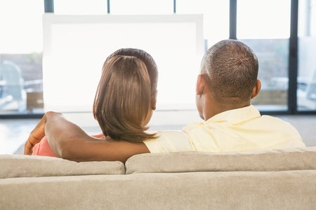 over the shoulder view: Over shoulder view of casual couple watching tv in living room Stock Photo