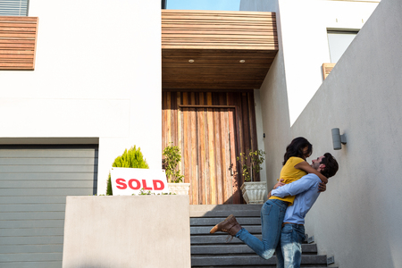 house moving: Happy Hispanic couple hugging in front of new house