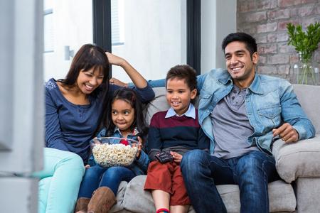 ver television: Familia de joven feliz comiendo palomitas de maíz mientras ve la televisión en la sala de estar