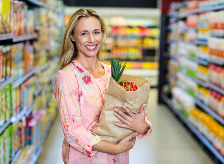 grocery bag: Pretty smiling woman holding grocery bag in the supermarket