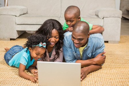 family sofa: Happy family lying on the floor using laptop in the living room Stock Photo
