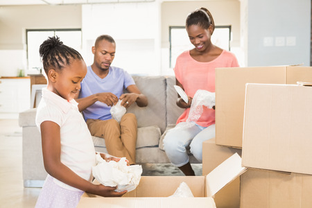 happy home: Family unwrapping things in new home in living room