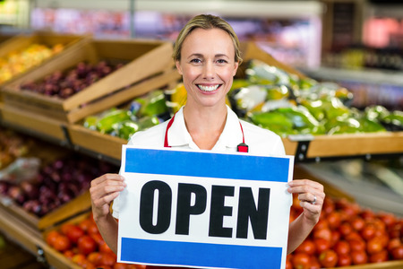 open business: Smiling woman holding sign at supermarket