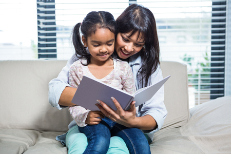 family with one child: Happy mother reading book with her daughter in living room