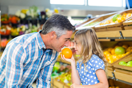 family with one child: Cute girl holding an orange to her father at the grocery shop